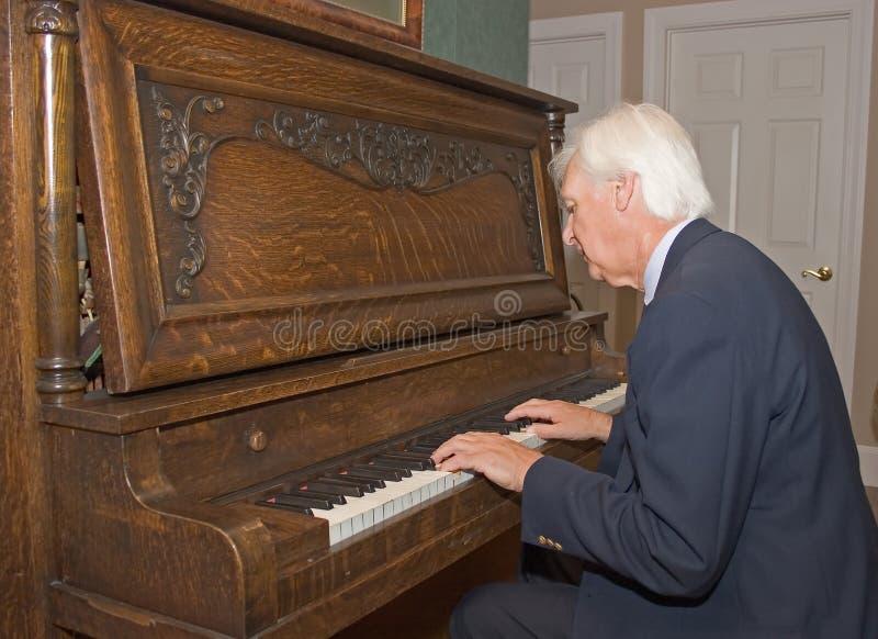 Homme aîné jouant le piano photos libres de droits