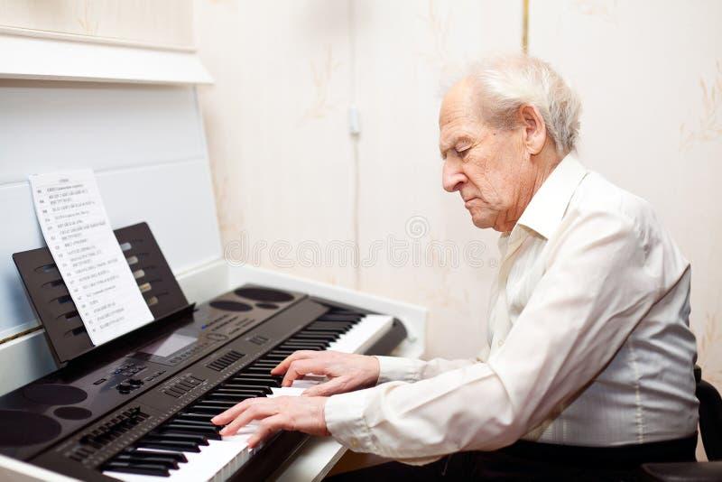 Homme aîné jouant le piano photo stock