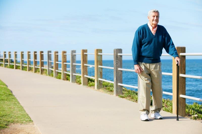 Homme aîné marchant le long du chemin par la mer image stock
