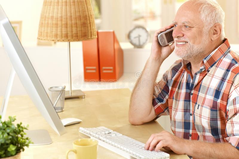Homme aîné parlant sur le portable, utilisant l'ordinateur photo libre de droits