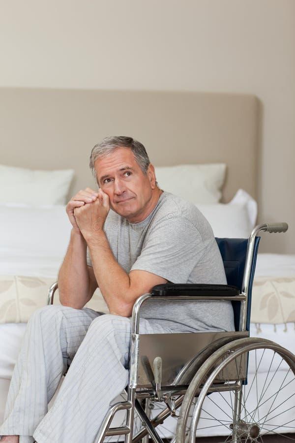 Homme aîné pensif dans son fauteuil roulant photo libre de droits