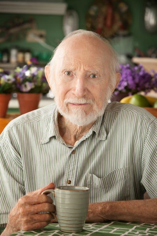 Homme aîné sérieux avec la tasse photographie stock