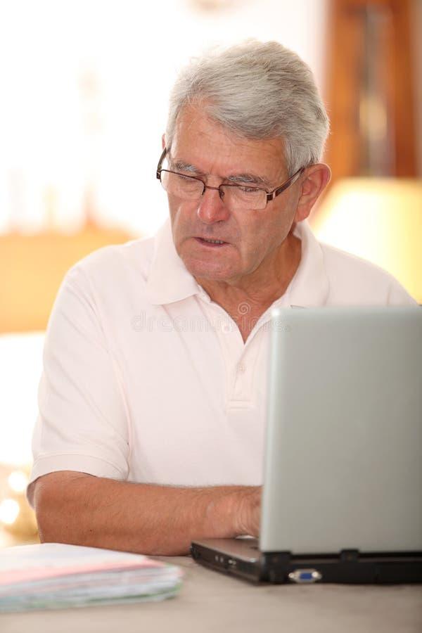 Homme aîné utilisant l'Internet image libre de droits