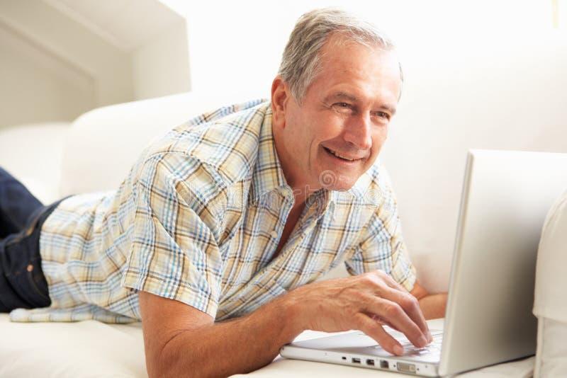 Homme aîné utilisant se reposer de détente d'ordinateur portatif sur le sofa images stock