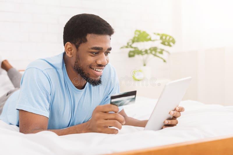 Homme achetant le produit en ligne, utilisant la carte de crédit pour payer photo libre de droits