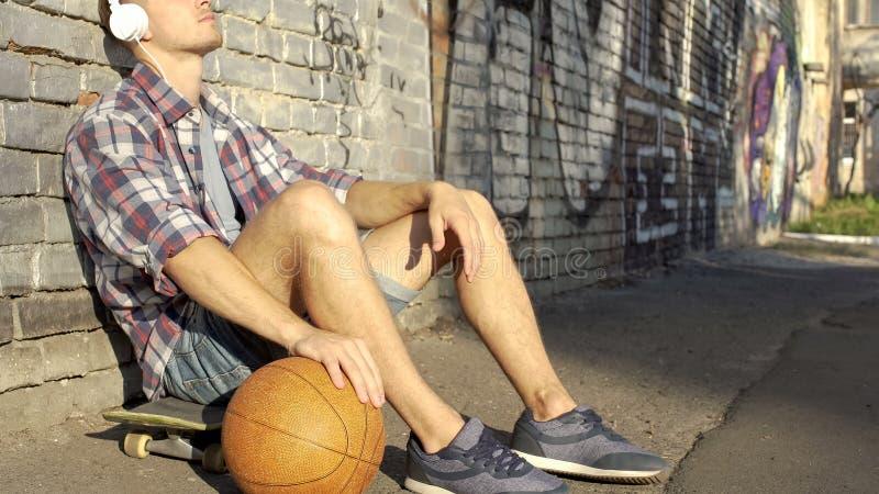 Homme actif s'asseyant sur la planche à roulettes, jouant la boule et écoutant la musique dans le casque photos libres de droits