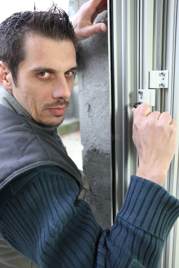 Homme adaptant une fenêtre image stock