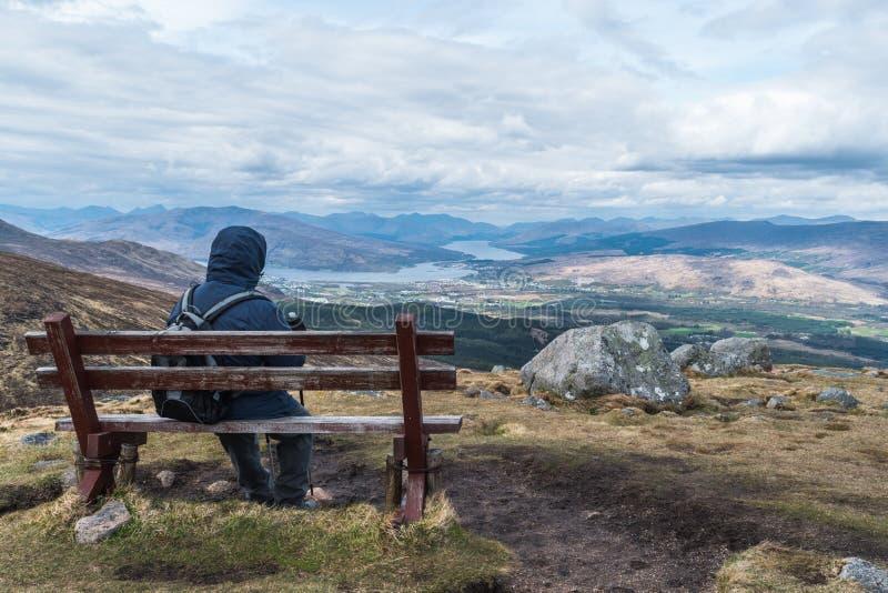 Homme admirant la vue de paysage sur un banc images stock
