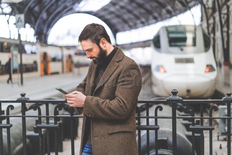 Homme adulte attirant employant l'application mobile sur son smartphone à la station de train Concept de course d'affaires photographie stock libre de droits