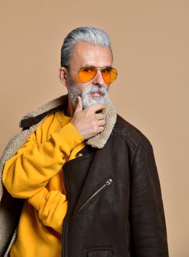 Homme adulte avec une barbe et moustache dans un manteau en cuir et un béret, un regard sévère, le studio sur un fond brun-bleu photo stock