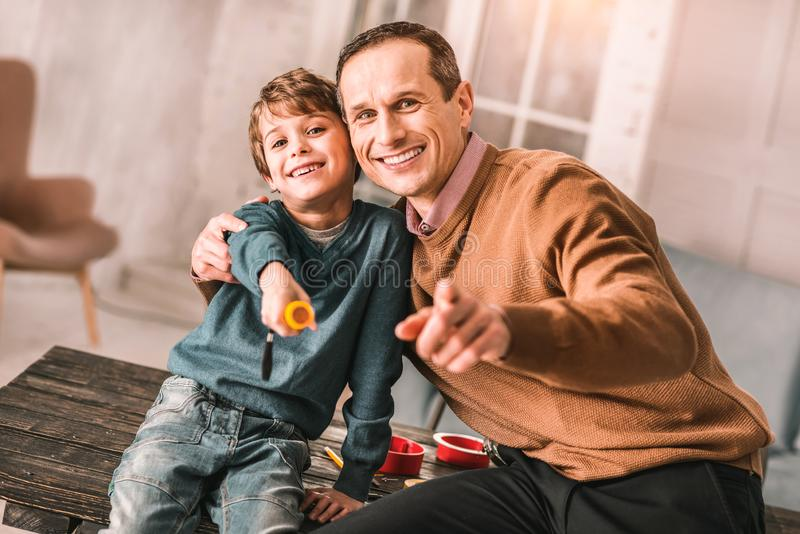 Homme adulte bel souriant sincèrement tout en posant avec son petit garçon photos stock