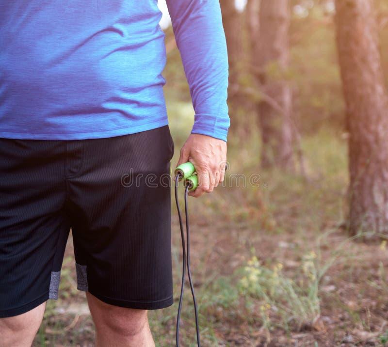 homme adulte dans des vêtements bleus tenant une corde de saut pour jouer des sports image libre de droits