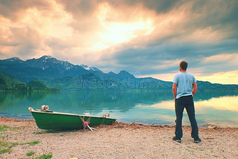 Homme adulte dans la promenade bleue de chemise au vieux bateau de palette de pêche à la côte de lac de montagnes photos libres de droits