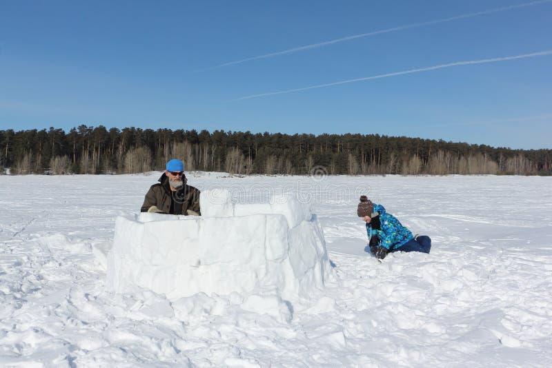 Homme adulte et petit garçon construisant un igloo sur la clairière neigeuse, Novosibirsk, Russie photos stock