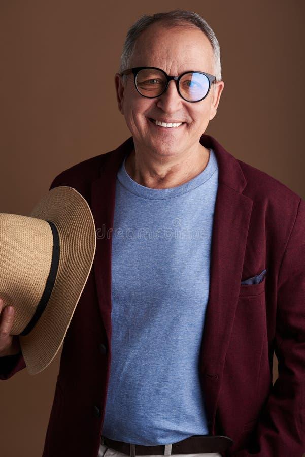 Homme adulte joyeux dans des vêtements élégants posant avec son chapeau de paille images libres de droits