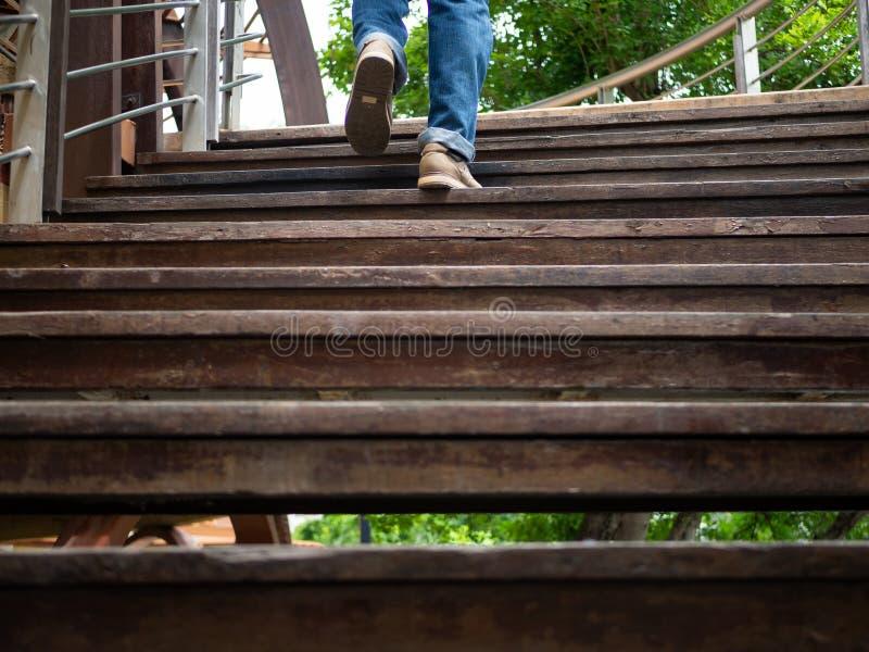 Homme adulte marchant vers le haut des escaliers en bois Faire avancer le concept images stock