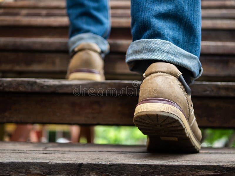 Homme adulte marchant vers le haut des escaliers en bois Faire avancer le concept images libres de droits