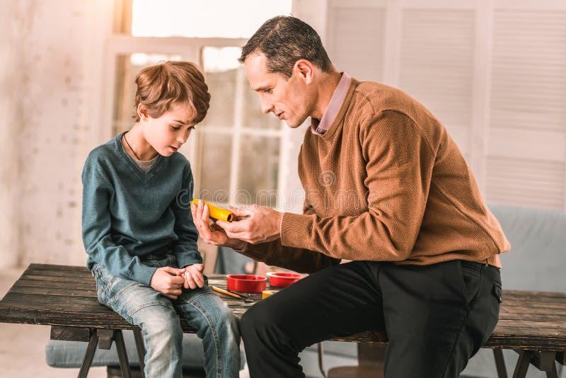Homme adulte passionné consacré présentant un dispositif vraiment frais à son jeune fils image libre de droits