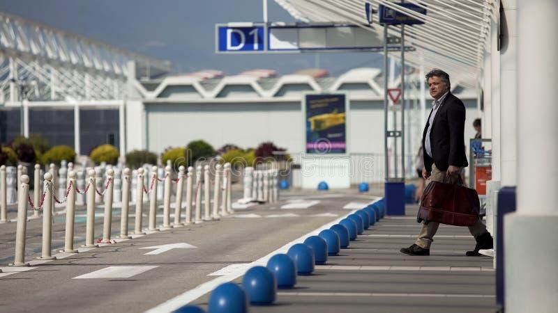 Homme adulte quittant l'aéroport, taxi de attente au centre de la ville, voyage d'affaires images stock