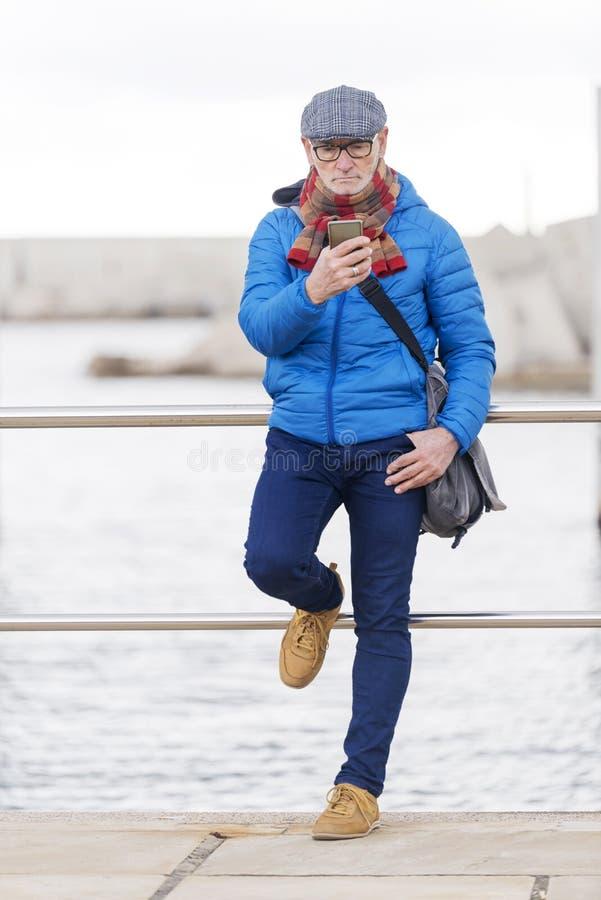 Homme adulte songeur utilisant la veste bleue et à l'aide du smartphone images stock