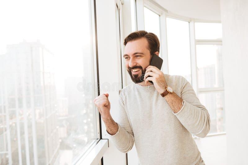 Homme affable avec la barbe et moustache regardant par la grande fenêtre, photo stock
