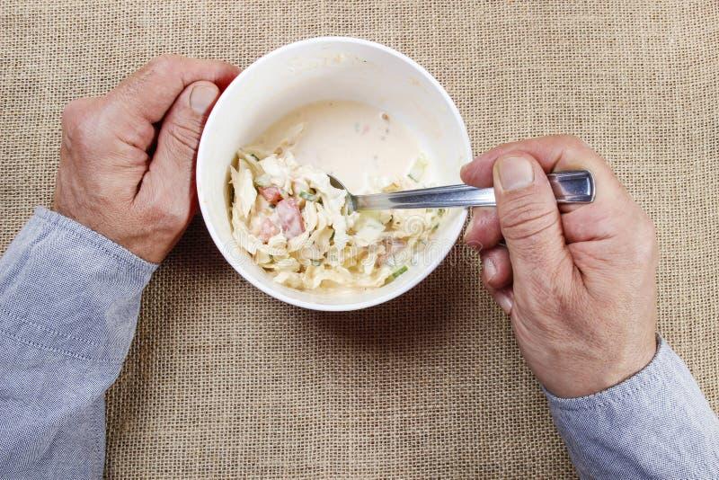 Homme affamé au-dessus de son repas. photographie stock libre de droits