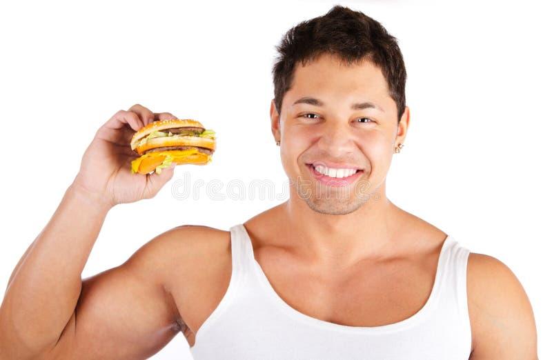 Homme affamé avec l'hamburger. au-dessus du fond blanc image stock