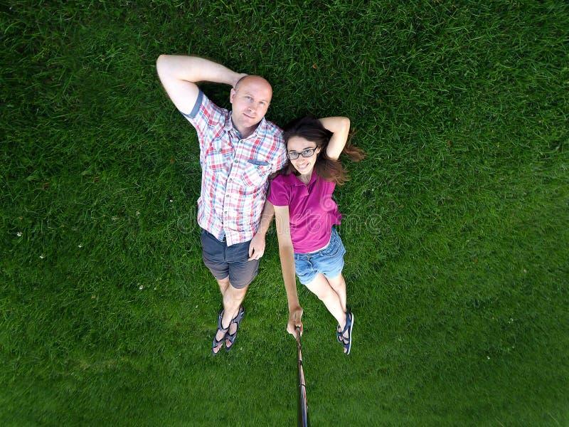 Homme affectueux et femme de couples se trouvant sur l'herbe verte image stock