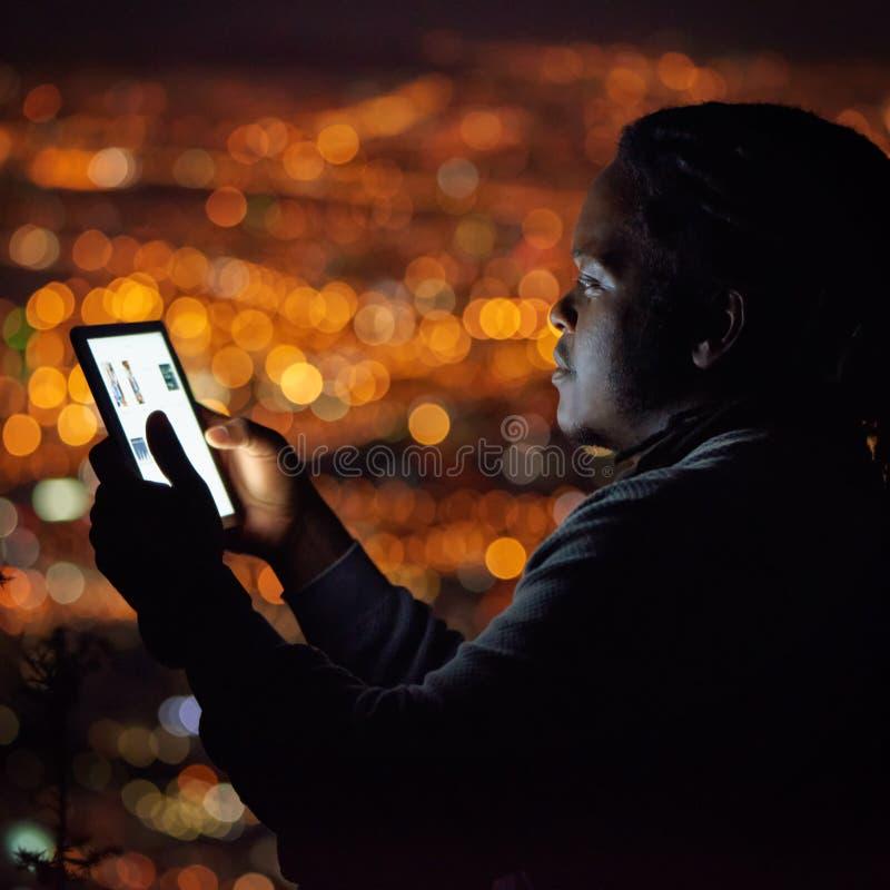 Homme africain à l'aide d'un comprimé la nuit avec le fond de paysage urbain photos libres de droits