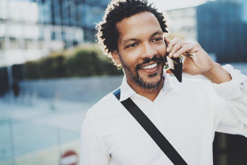 Homme africain américain de sourire à l'aide du smartphone pour appeler des amis à la rue ensoleillée Concept des jeunes beaux he images stock
