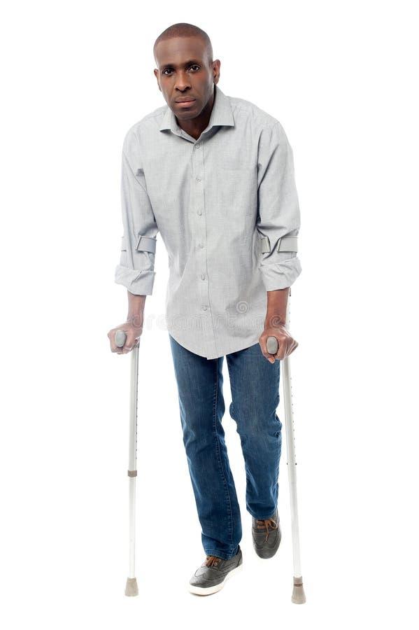 Homme africain avec des béquilles essayant de marcher photos stock