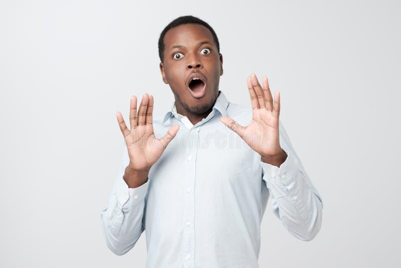 Homme africain ayant stupéfié et sembler choqué écoutant l'histoire d'amis dans l'incrédulité images stock