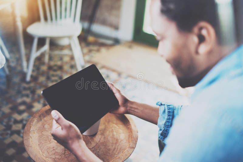 Homme africain barbu attirant à l'aide de l'ordinateur portable tout en détendant sur le fauteuil dans le bureau moderne Concept  photographie stock