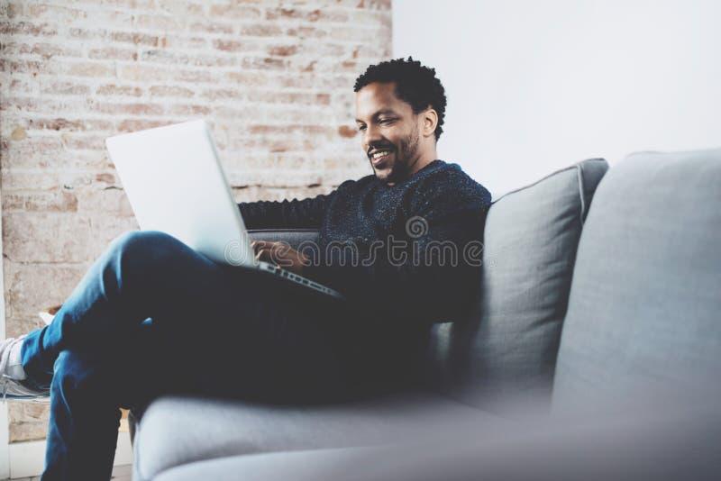 Homme africain barbu gai travaillant sur l'ordinateur portable tout en reposant le sofa à son endroit moderne de bureau Concept d image stock