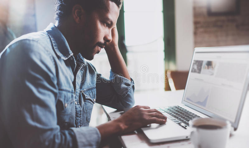 Homme africain barbu travaillant sur l'ordinateur portable tout en passant le temps à la maison Concept des gens d'affaires à l'a image libre de droits