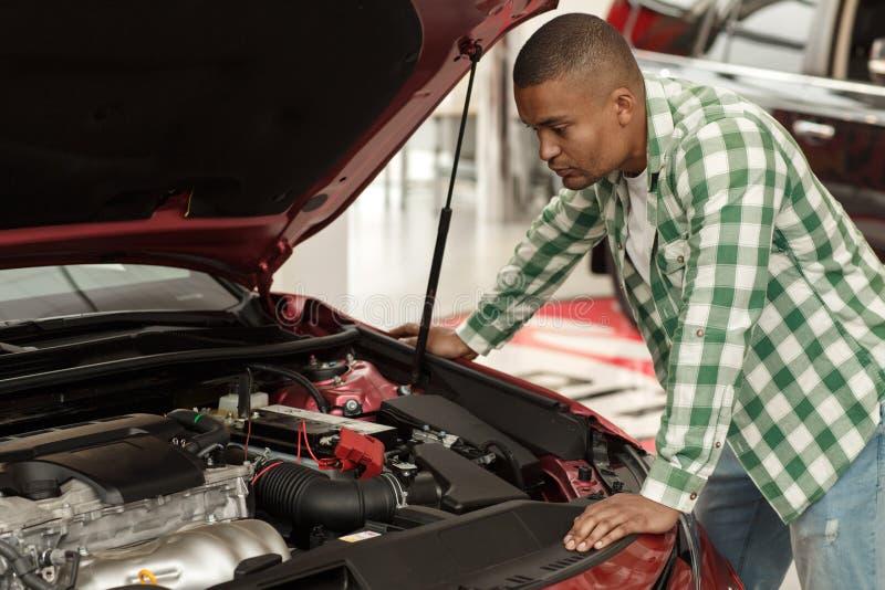 Homme africain bel choisissant la nouvelle voiture au concessionnaire photo libre de droits
