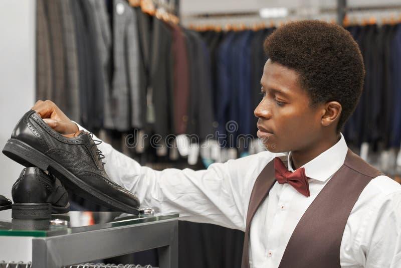 Homme africain bel choisissant les chaussures noires dans le magasin photographie stock