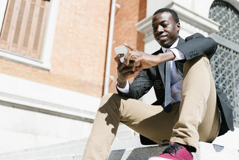 Homme africain bel employant son mobile images stock