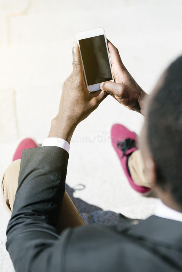 Homme africain bel employant son mobile image libre de droits