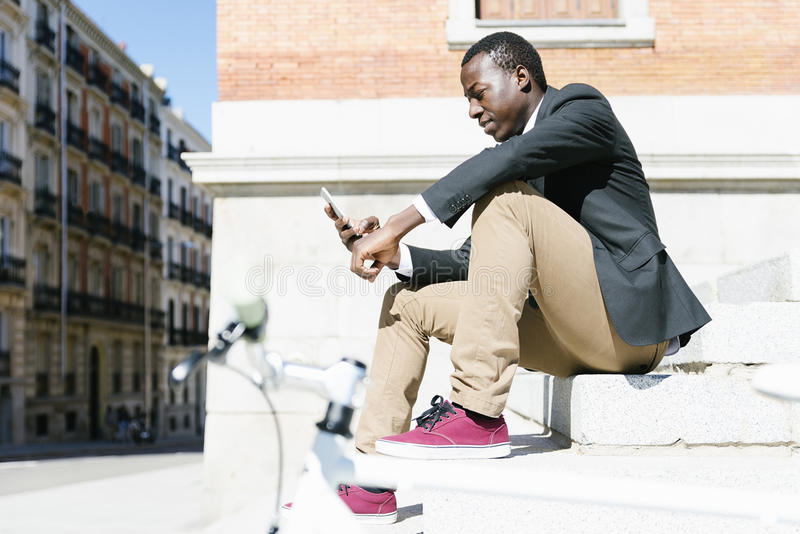 Homme africain bel souriant quand il emploie son mobile photo stock