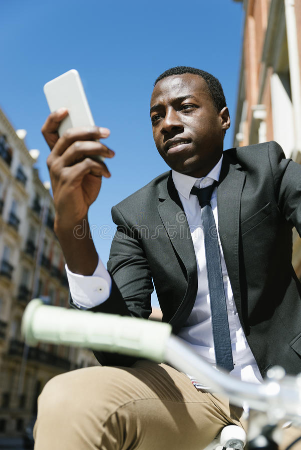 Homme africain bel souriant quand il emploie son mobile photos stock
