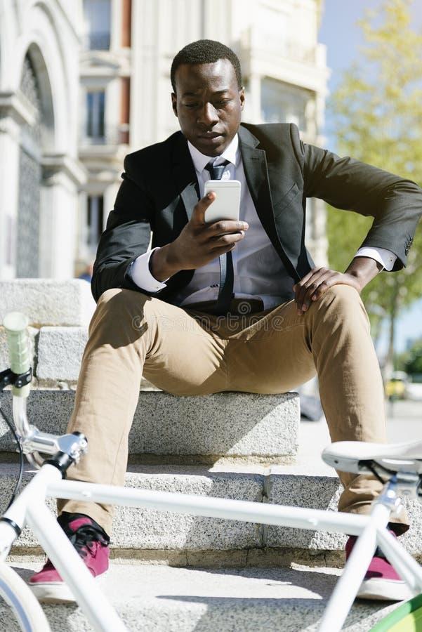 Homme africain bel souriant quand il emploie son mobile photos libres de droits