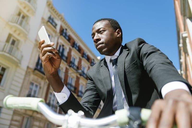 Homme africain bel souriant quand il emploie son mobile photo libre de droits