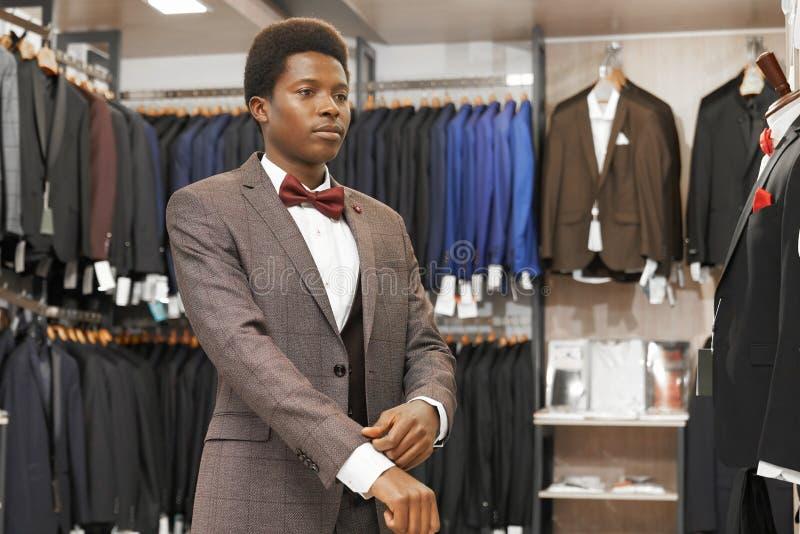 Homme africain choisissant le costume élégant dans la boutique à la mode photo stock