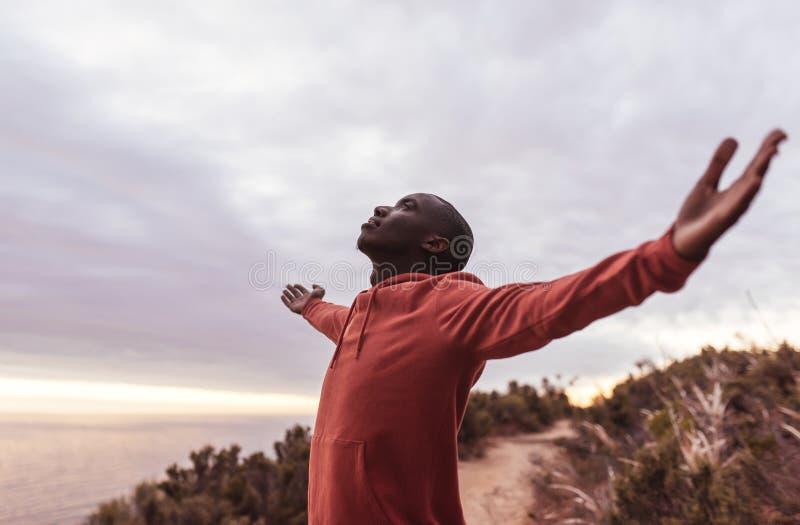 Homme africain convenable se tenant sur une traînée embrassant dehors la nature images libres de droits