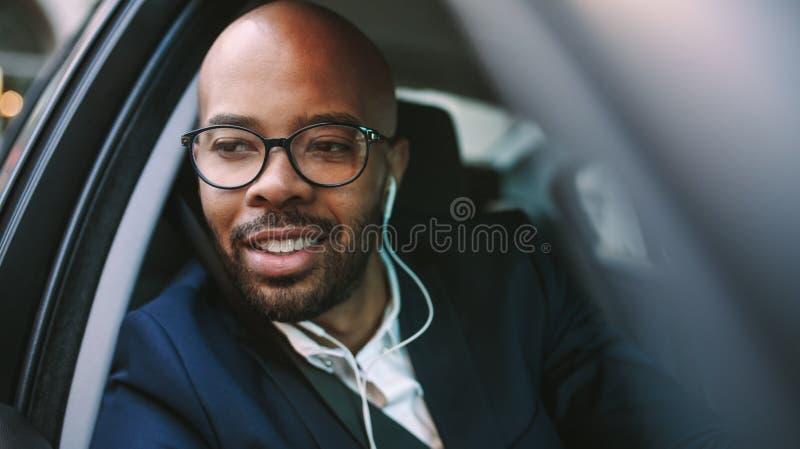 Homme africain d'affaires conduisant la voiture au bureau photographie stock