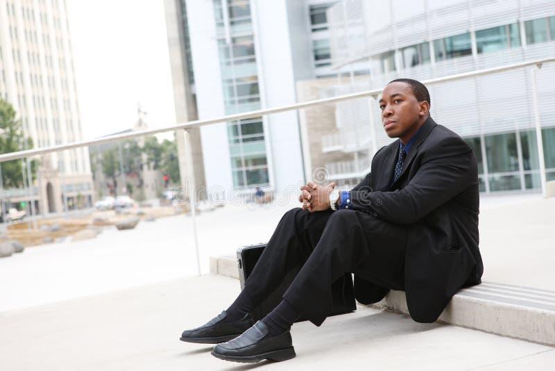 Homme africain d'affaires s'asseyant à l'immeuble de bureaux photos stock