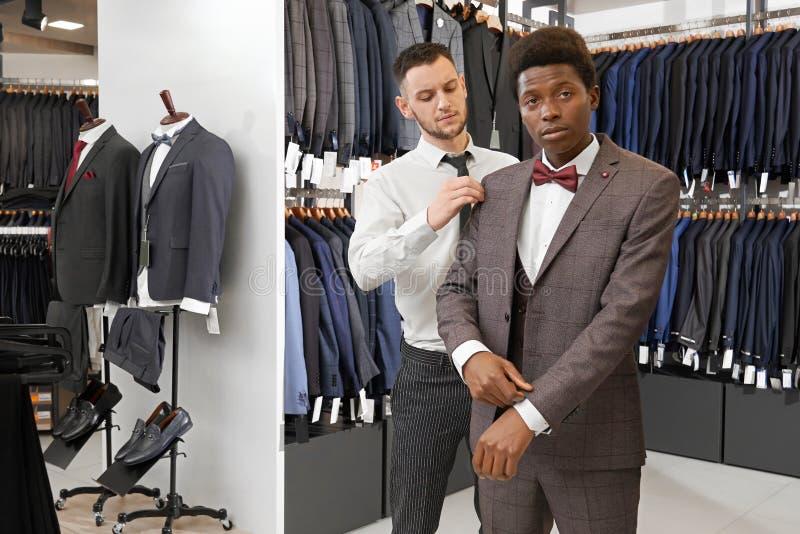 Homme africain dans la boutique essayant, choisissant le costume élégant photos stock