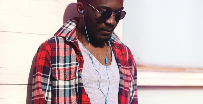 Homme africain de portrait de mode le jeune écoute la musique dans des écouteurs photo stock