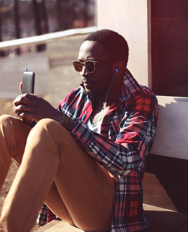 Homme africain de portrait de mode le jeune écoute la musique utilisant le smartphone photos libres de droits